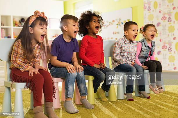 Group of mischief kids sitting at preschool and screaming.