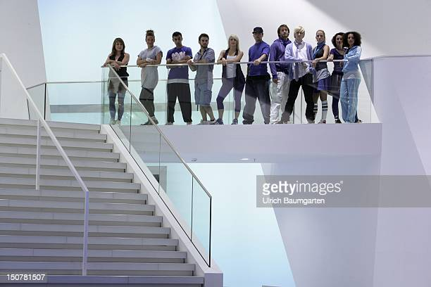 MAIN Group of modern female and male young people above stairs at the banister of a passage
