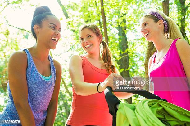 Group of moms exercising together in park with jogging strollers