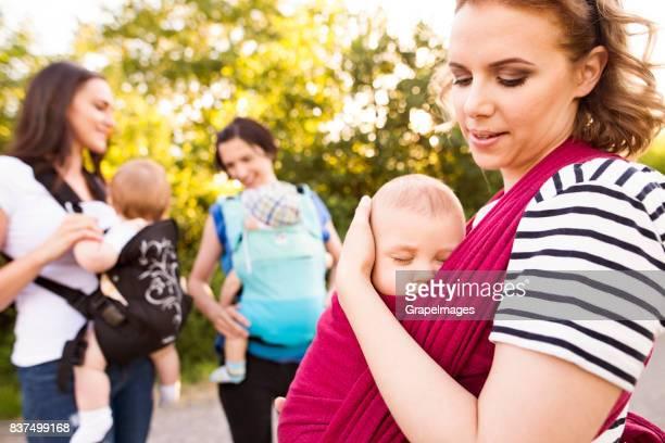 Groupe de mères sur pied avec leur bébé.