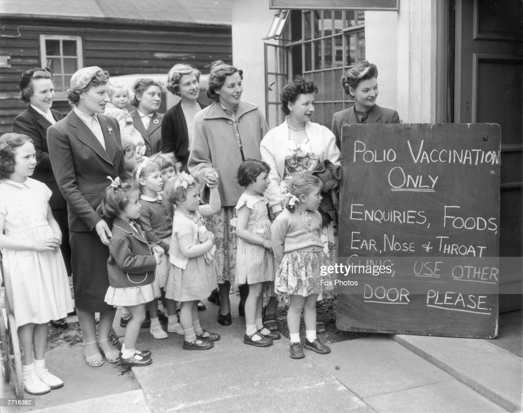 A group of mothers with their children wait outside the Middlesex County Council Clinic for the first polio vaccinations to begin 8th May 1956