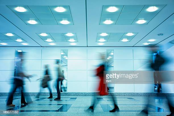 Group of Motion Blurred People Walking Through Illuminated Corridor