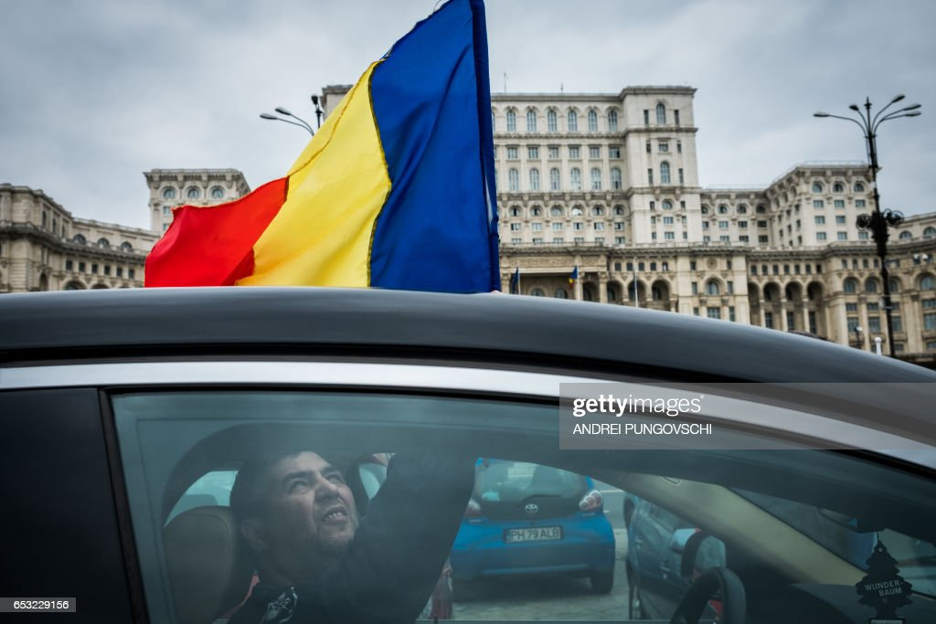 A group of motorists take part in a protest against corruption outside the Romanian parliament, on March 14, 2017, in Bucharest. Dozens of drivers protested against corruption by driving at the lower speed limit and deliberately slowing down traffic. /