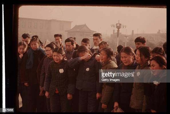 A group of mourners stand together in grief as they wait their turn to see the body of Premier Chou En Lai January 13 1976 in Peking China EnLai was...