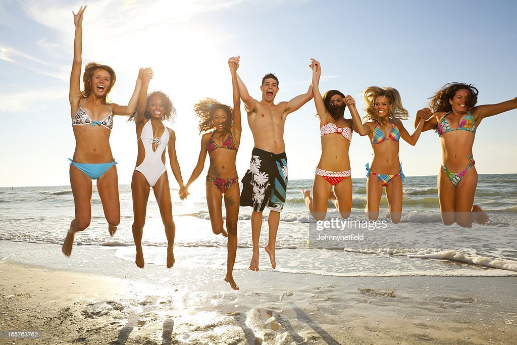 Group of multi ethnic friends at beach jumping