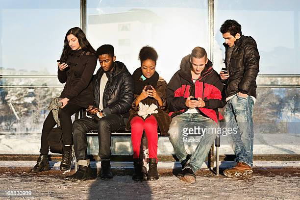 Group of multi ethnic friends using mobile phones on bench