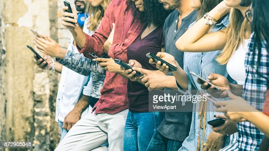 Group of multicultural friends using smartphone outdoors - People hands addicted by mobile smart phone - Technology concept with connected men and women - Shallow depth of field on vintage filter tone : Stock Photo