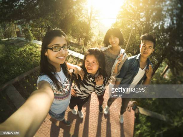 Group of multiethnic college friends taking selfie.