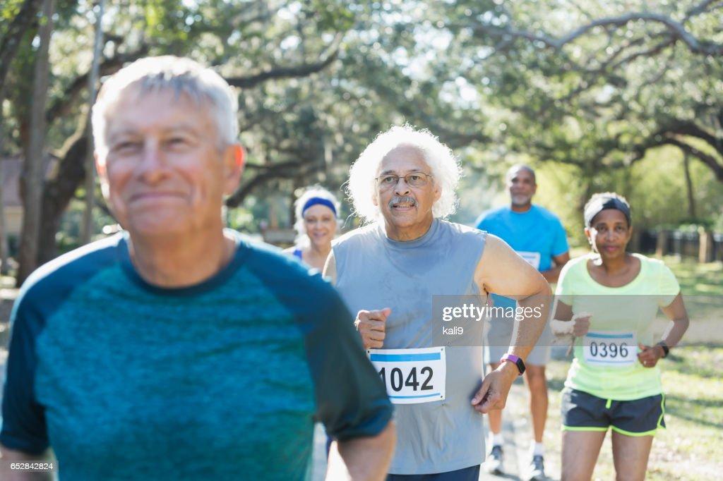 Group of multi-ethnic seniors running a race : Stockfoto