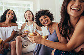 Group of multiracial friends at a party and smiling. Women friends having a party at home and looking away.