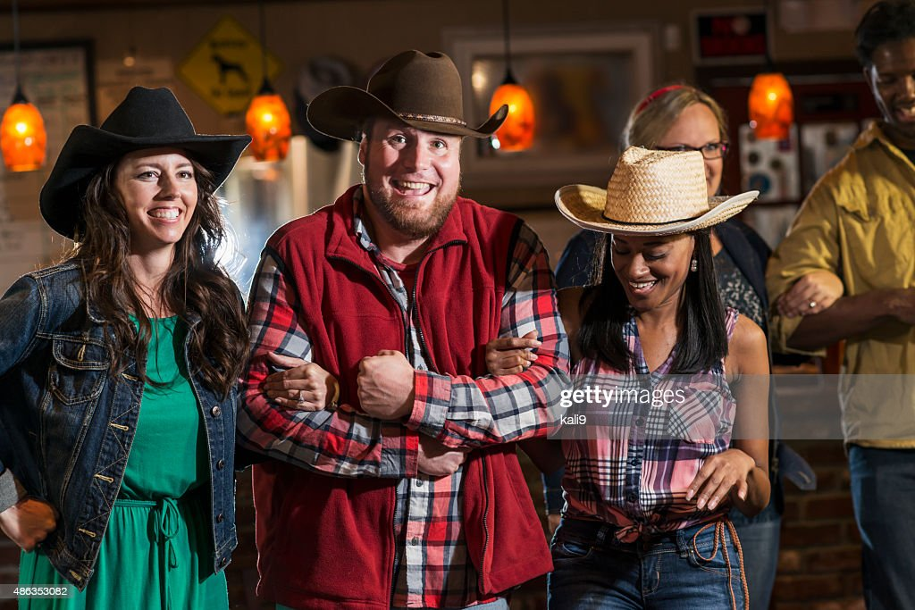 Group of multiracial friends dancing in cowboy hats : Stock Photo