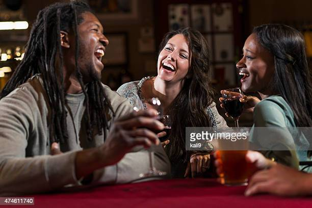 Group of multiracial friends drinking and laughing