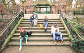 Group of multiracial friends using mobile smart phone sitting on stairs at park - Young hipster people addicted by smartphone on social network community - Technology concept - Desaturated color tones