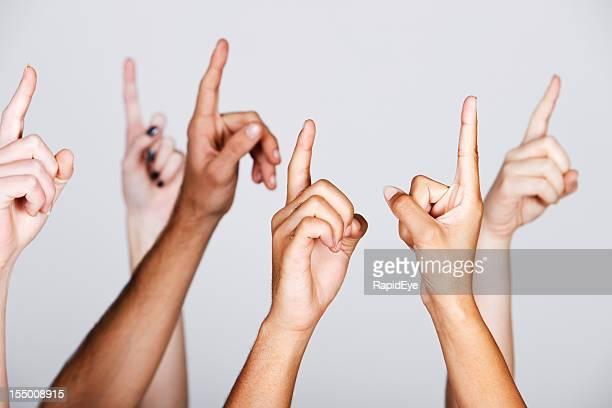 グループの様々な人種の手を上に揚げる動作点