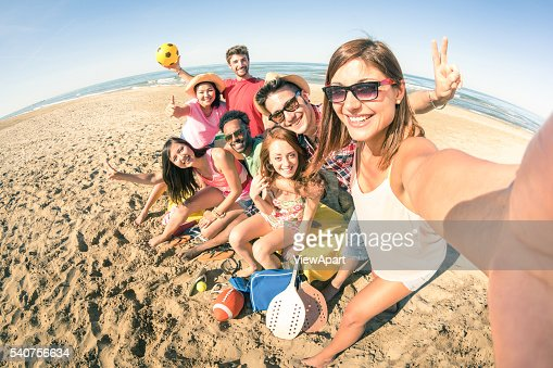 Group of multiracial happy friends taking fun selfie at beach : Foto stock