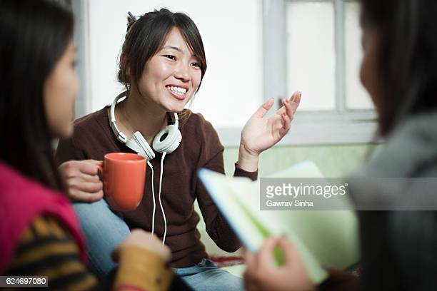 Group of multiracial late teen Asian students girls discussing together.
