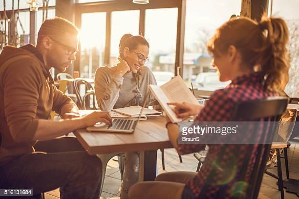 Eine Gruppe von Multitasking college-Studenten in einem Café.