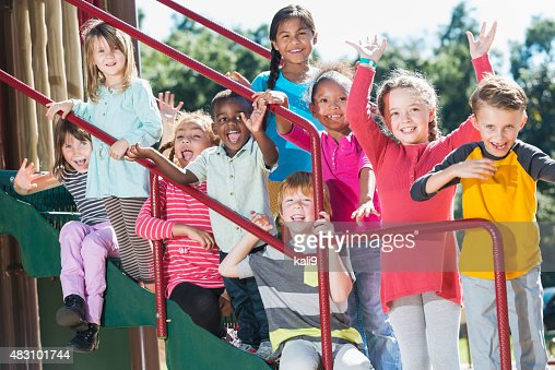 Group of multracial children waving on a playground