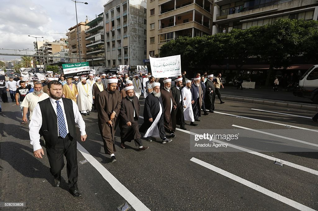 A group of Muslim scholars hold signs reading 'Aleppo is burning, Help Aleppo' protest and march against the air strikes conducted by the Assad regime and Russia over the Aleppo in front of Russian embassy building in Beirut, Lebanon on May 4, 2016.