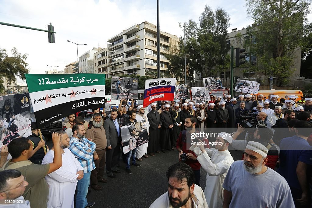 A group of Muslim scholars hold signs reading 'Aleppo is burning, Help Aleppo' and protest against the air strikes conducted by the Assad regime and Russia over the Aleppo in front of Russian embassy building in Beirut, Lebanon on May 4, 2016.