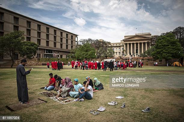 A group of Muslim students pray as lecturers and staff of Witwatersrand University demonstrate in support of the free education movement and against...