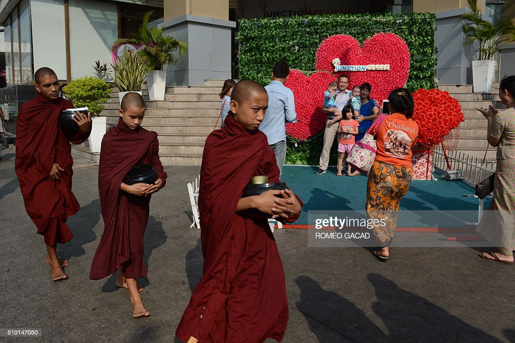A group of Myanmar Buddhist monks walks by a family (back R) posing in front of a Valentine's Day display of plastic flowers outside a shopping center in Yangon on February 14, 2016. Valentine's Day celebration is largely promoted by commercial centres and many Myanmar couples go out on dates and present simple gifts to one another. AFP PHOTO / ROMEO GACAD / AFP / ROMEO GACAD
