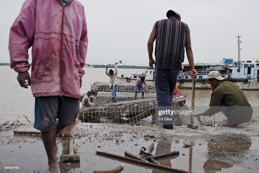 A group of Myanmar men work to demolish an old pier on the ...