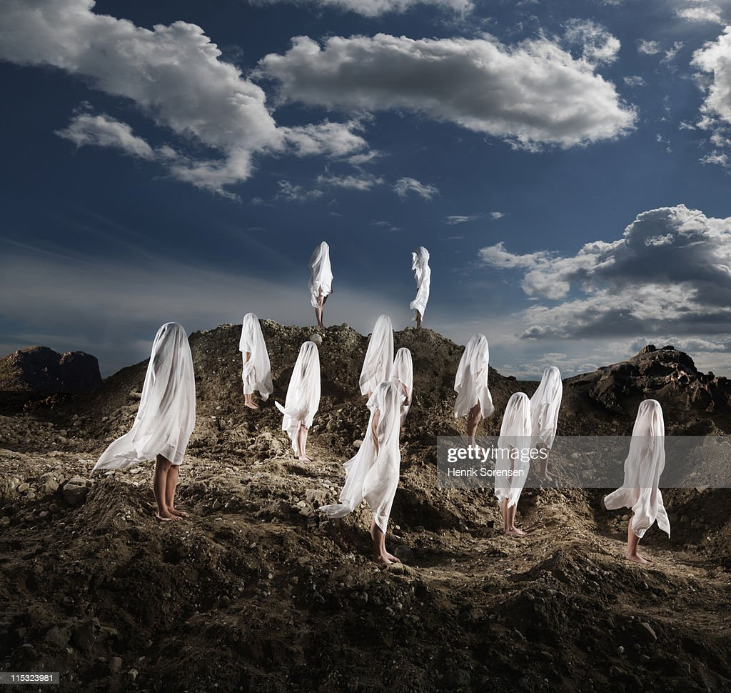 group of naked people covered with white linnen : Stock Photo