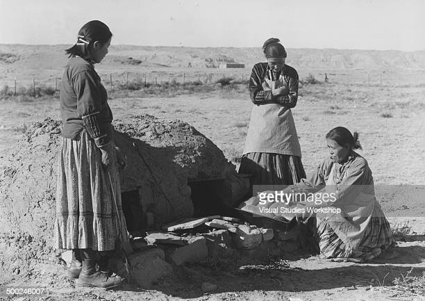 A group of Navajo Indian women bake bread using a horno or mud adobebuilt outdoor oven at the day school early to mid 20th century Many adults in the...