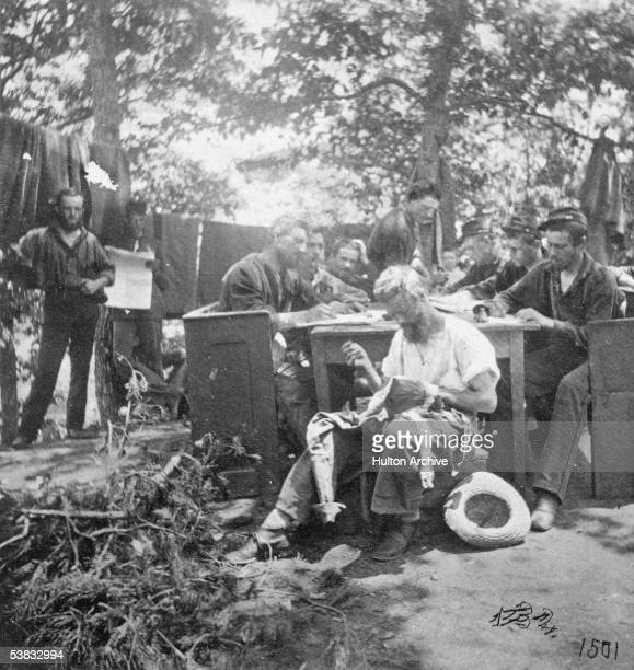 A group of Northern soldiers from the Army of the Potomac takes advantage of a respite from battle to write letters and mend clothing during the...
