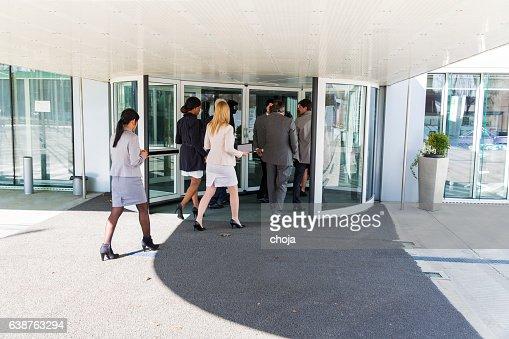 Group of ofiice worker entering in  revolving door