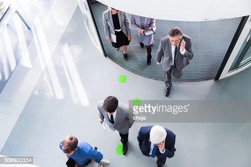 Group of ofiice worker entering through revolving door