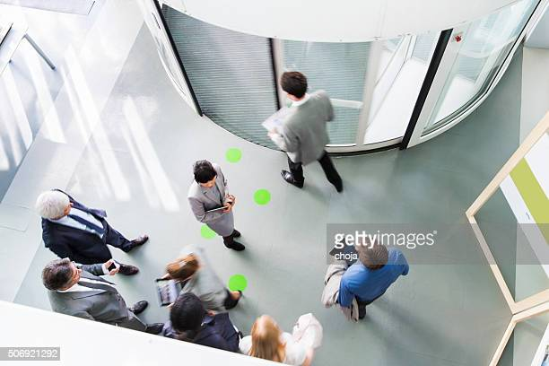 Group of ofiice worker entering through revolving door