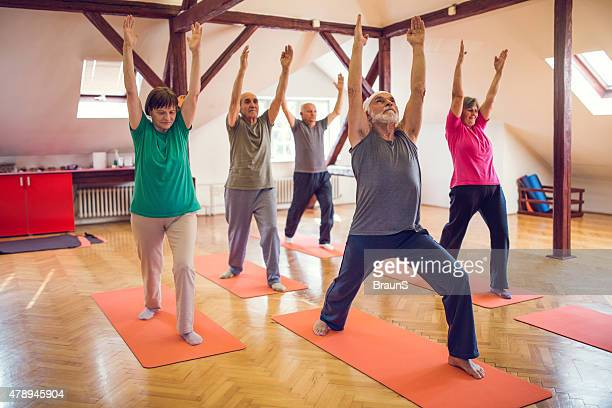 Group of old people doing stretching exercises with raised arms.