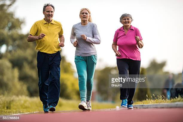 Group of old people jogging on running track outdoors.