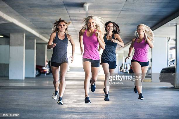 Group of only women running inside a parking