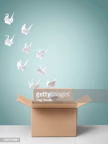Group of origami cranes flying away from cardboard