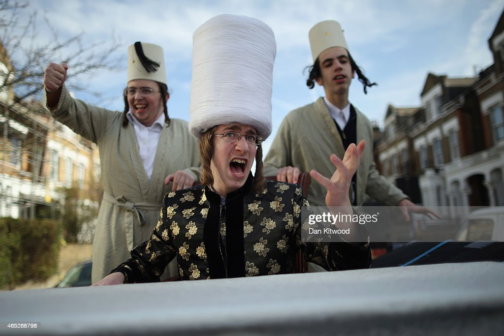 A group of Orthodox Jewish boys dance and sing outside the home of a local businessmen while collecting money for their school during the Jewish...