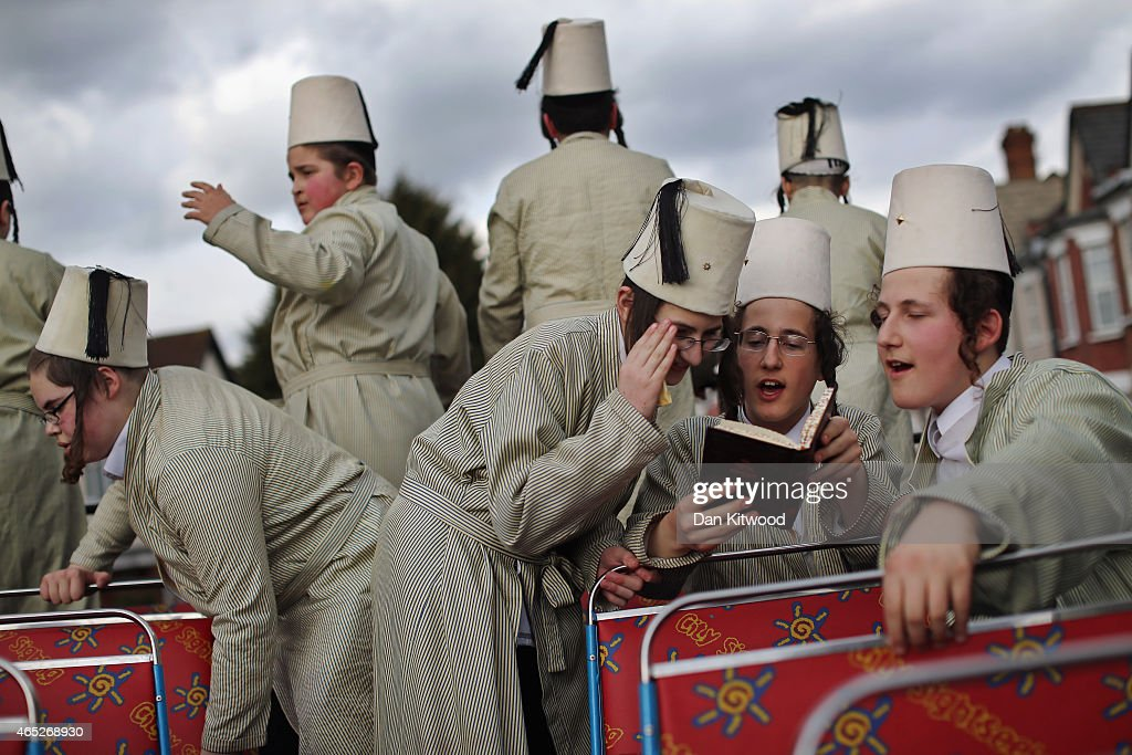 A group of Orthodox Jewish boys read sections of the Megillah while riding through the streets on an open top bus during the Jewish holiday of Purim...
