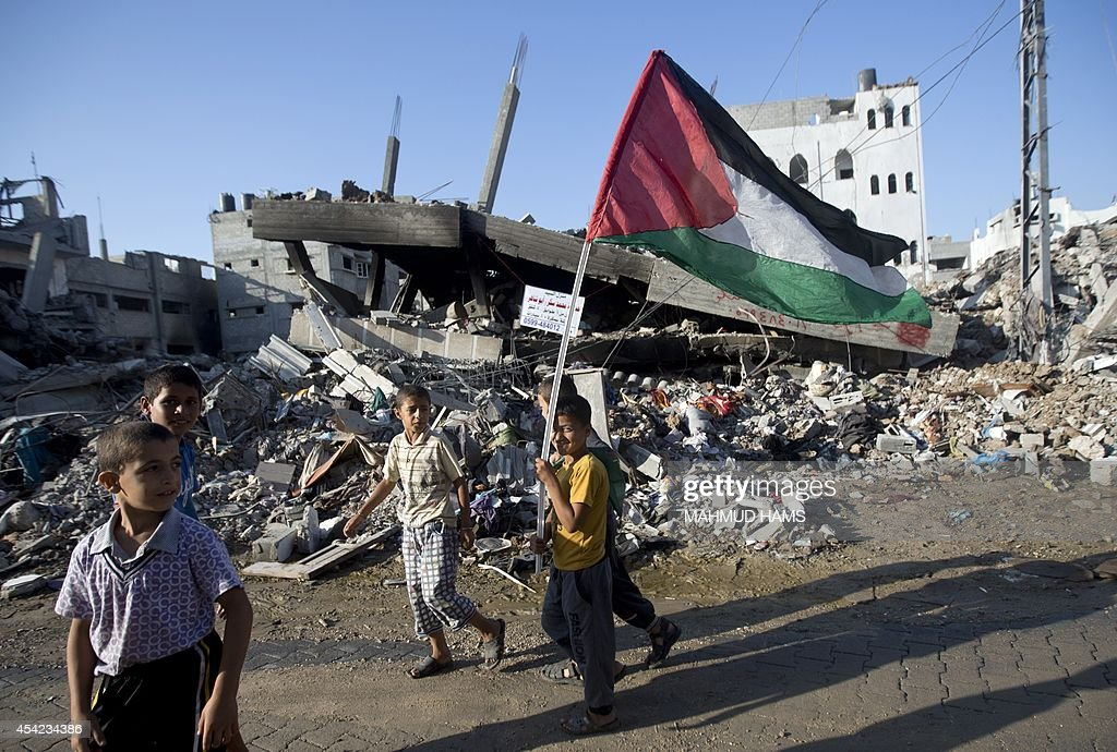 A group of Palestinian boys one carrying the national flag walk past destroyed houses in the Shejaiya neighborhood of Gaza City on August 27...