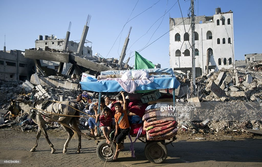 A group of Palestinian boys ride horse-drawn cart past destroyed houses in the Shejaiya neighborhood of Gaza City on August 27, 2014, following the long-term truce agreed between Israel and the Palestinians. After seven weeks of the deadliest Israeli-Palestinian violence in a decade, a long-term ceasefire took hold at 1600 GMT on August 26, sparking festivities around the Gaza Strip.