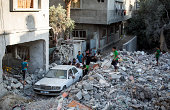 A group of Palestinian men push a car that had become trapped by rubble out of an area of destroyed housing on August 16 2014 in Gaza City Gaza A...