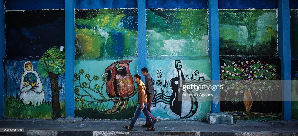 A group of Palestinian painter draw a pictures on the wall of buildings belonging to the United Nations Relief and Works Agency for Palestine Refugees in the Near East (UNRWA) in Gaza City, Gaza on June 25, 2016.