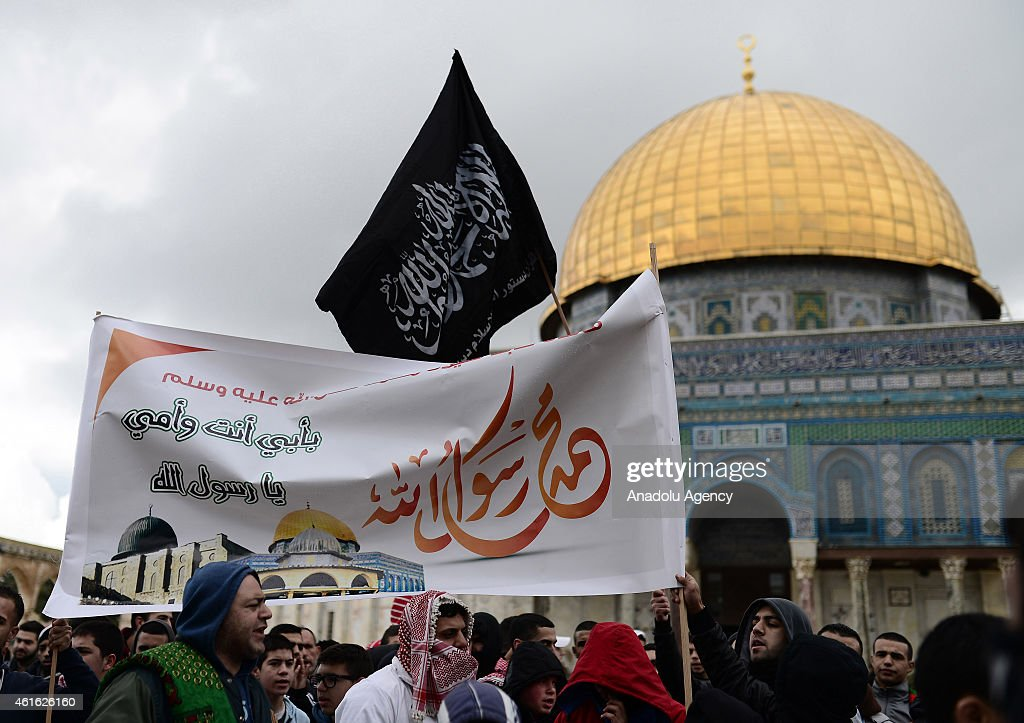 A group of Palestinians hold banners during protest against the French satirical weekly Charlie Hebdo outside Al-Aqsa Mosque following Friday prayer in Jerusalem on January 16, 2015.