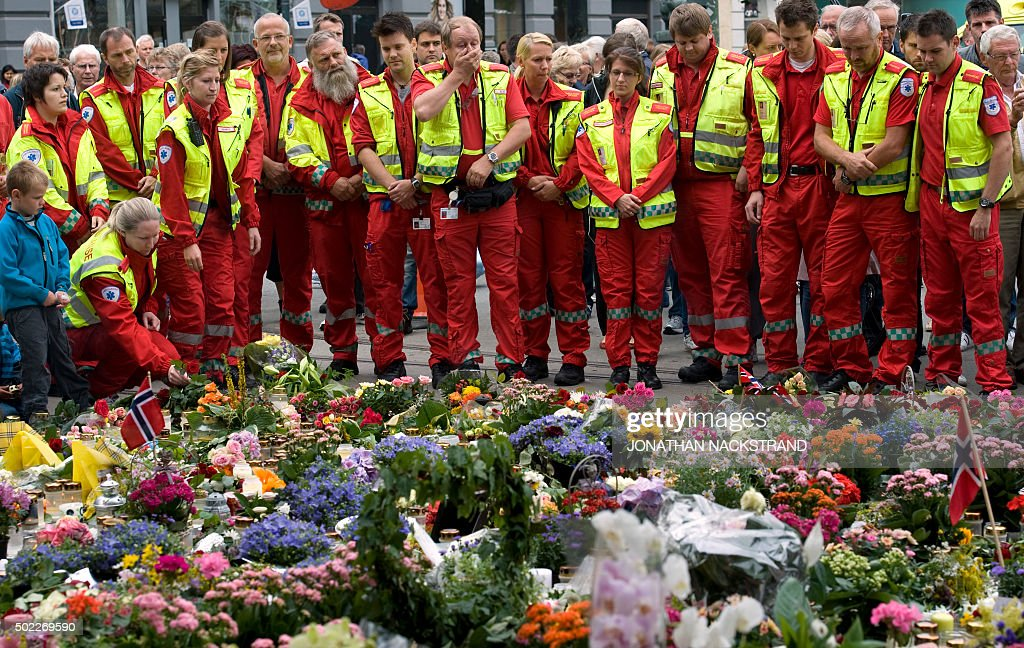 A group of paramedics place flowers on a makeshift memorial outside the Domkirken church in Oslo on July 25 2011 A minute of silence was observed...