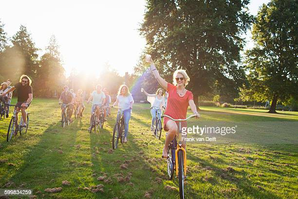 Group of partygoing adults arriving on cycles to sunset park party