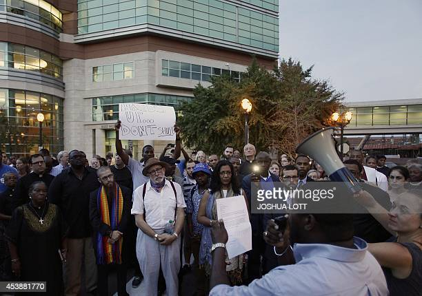 A group of pastors clergy and protesters stand outside the office building of St Louis County Prosecutor Bob McCullough on August 20 2014 in Clayton...