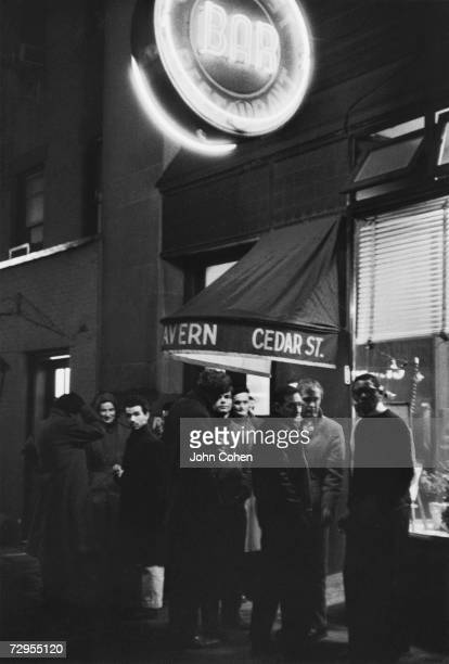 A group of patrons stands around on the sidewalk under the neon sign of the Cedar Street Tavern Univeristy Place Greenwich Village New York 1959