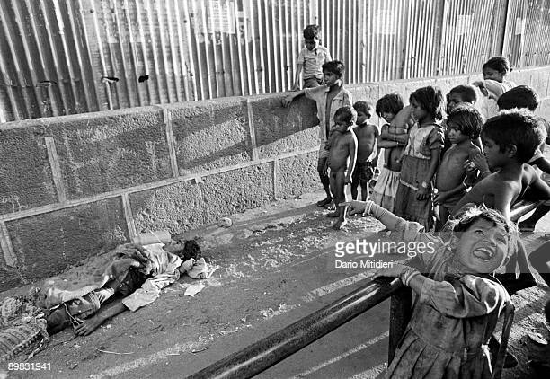 A group of pavement and street children gather around the body of a vagrant near Crawford Market in Bombay
