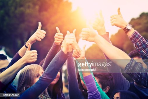 Group of people all raising arms with thumbs up